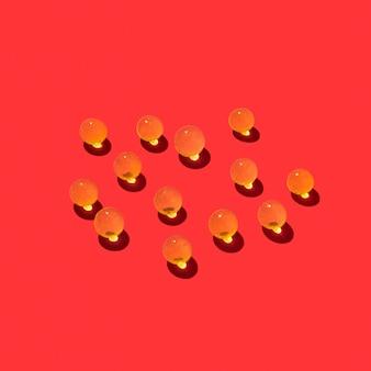 Modello creativo da sfere di idrogel di liquido cristallino con ombre e riflessi su una parete rossa, copia dello spazio.