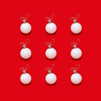 Modello creativo con palline bianche di capodanno, giocattoli per le vacanze su rosso brillante
