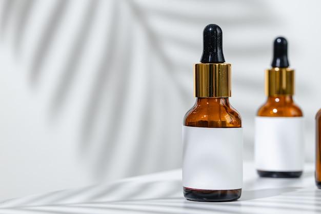 Foto creativa della bottiglia cosmetica con pipetta su uno sfondo bianco con ombra di fiori tropicali. pubblicità