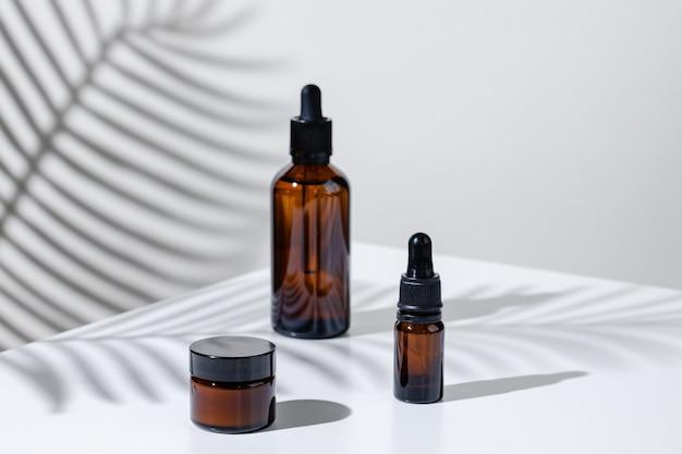 Foto creativa della bottiglia cosmetica con pipetta su uno sfondo bianco con ombra di fiori tropicali.