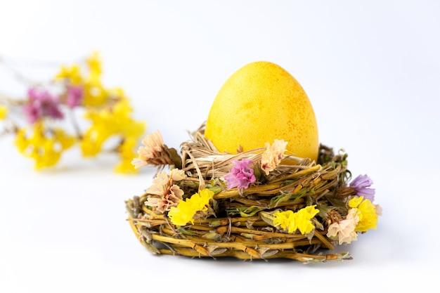 Foto creativa con nido di uova gialle di pasqua e fiori gialli