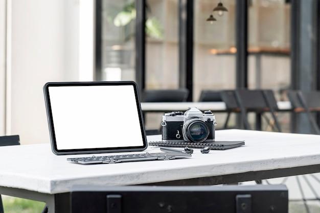 Area di lavoro del fotografo creativo. tablet schermo vuoto e tastiera, fotocamera e auricolare sul tavolo di legno all'aperto.