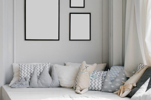 Cuscini creativi nella stanza dei bambini in passerella e cornici con spazio vuoto, modelli sul muro della casa