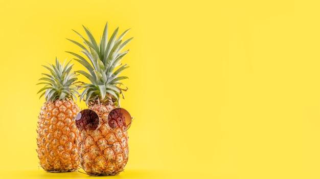 Ananas creativo che osserva in su con gli occhiali da sole e le coperture isolate, spiaggia di vacanze estive