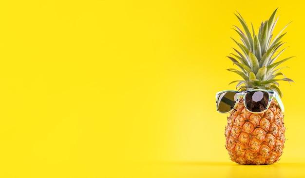 Ananas creativo che osserva in su con gli occhiali da sole e le coperture isolate, spiaggia di vacanze estive Foto Premium
