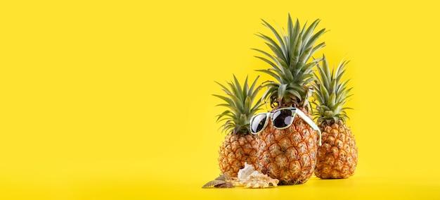 Ananas creativo che osserva in su con gli occhiali da sole e il guscio isolato su priorità bassa gialla, fine dello spazio della copia su