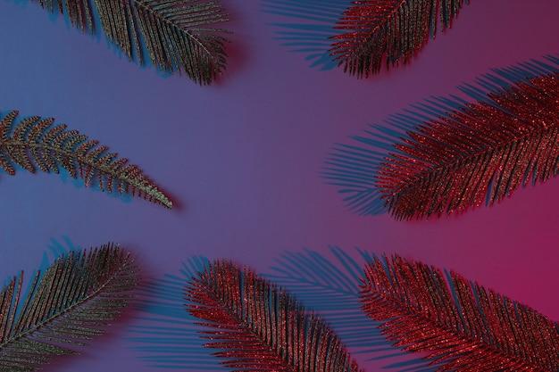 Concetto tropicale creativo pop art. foglie di palma d'oro su sfondo sfumato al neon blu-rosso.