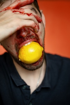 Ritratto creativo di un uomo con un limone su sfondo rosso