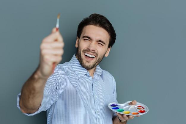 Processo creativo. felice simpatico uomo felice in possesso di una tavolozza di colori e guardando il pennello mentre vi godete l'arte