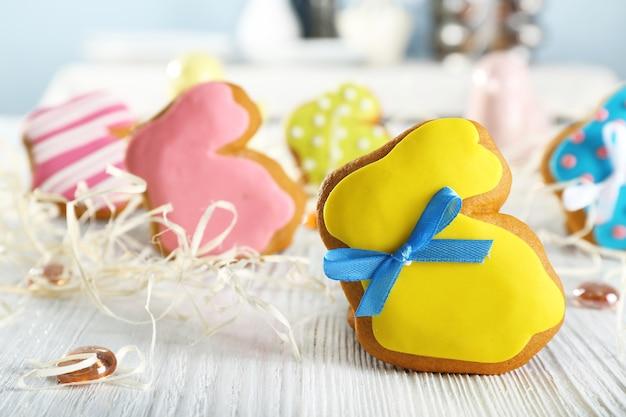 Biscotto di pasqua a forma di coniglio creativo e decorazioni su tavola di legno, primo piano