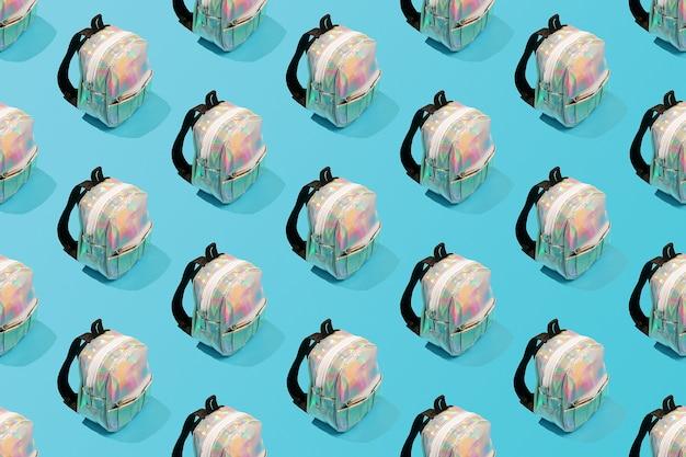 Motivo ripetuto creativo di uno zaino scolastico su sfondo blu.
