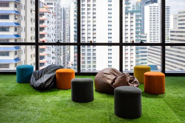 Spazio di coworking camera creativa con cuscini e sedie su erba artificiale in un ufficio moderno