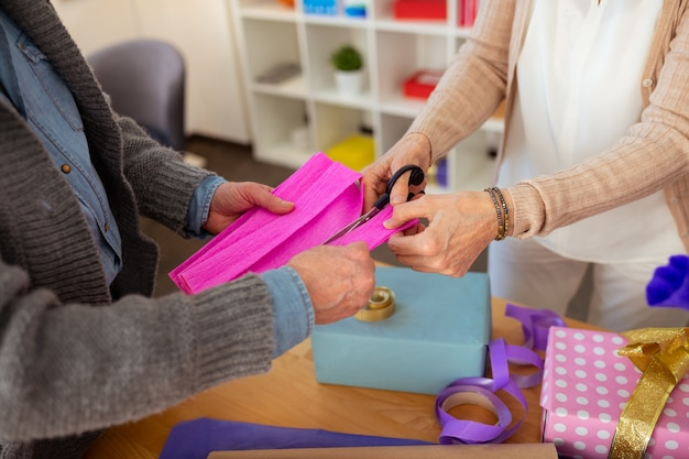 Soluzioni creative. primo piano di una carta da imballaggio tagliata mentre si decorano le scatole regalo