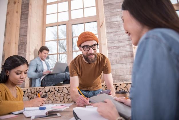 Spazio creativo. smart positivo giovane uomo in piedi vicino al tavolo e prendere appunti mentre si lavora con il suo team su un progetto