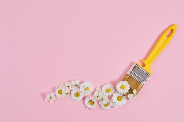 Concetto creativo del fiore di primavera. pennello con fiore su sfondo rosa pastello. tempo di primavera