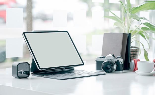 Studio creativo con tablet schermo vuoto, fotocamera e gadget sul tavolo superiore bianco.