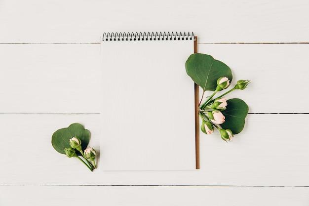 Mockup creativo ed elegante con foglie verdi e rose rosataccuino vuotodisposizione piatta minimalista
