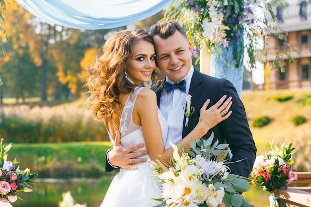 Cerimonia di matrimonio alla moda creativa elegante sposa e sposo ricci all'aperto sullo sfondo del lago