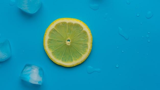 Composizione di sfondo estivo creativo con fetta di limone e cubetti di ghiaccio. il minimo concetto di bevanda limonata dall'alto verso il basso. copia spazio.