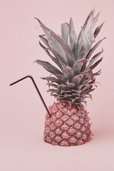 Una composizione estiva creativa con un ananas e un tubo da cocktail. il concetto di una bevanda minima all'ananas.