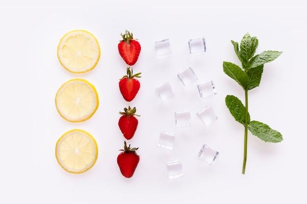 Composizione creativa di bevande estive. con fette di limone, foglie di menta, fragola e cubetti di ghiaccio su sfondo bianco