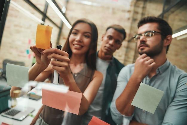 Team creativo gruppo misto di uomini d'affari che pianificano il processo di lavoro e utilizzano adesivi colorati