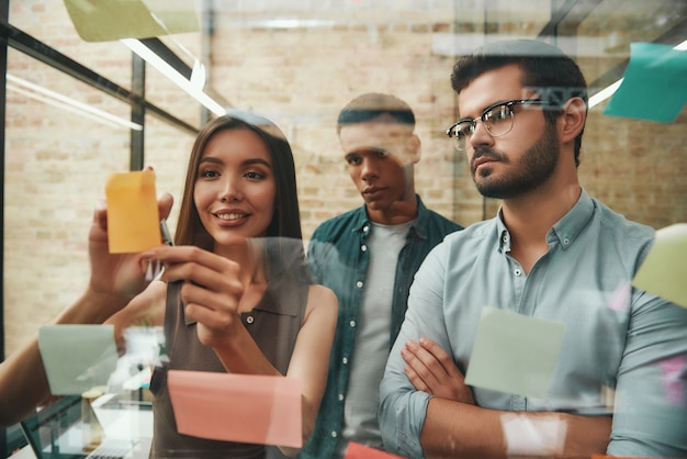 Team creativo di colleghi maschi e femmine intelligenti che pianificano il processo di lavoro e utilizzano schede memo mentre