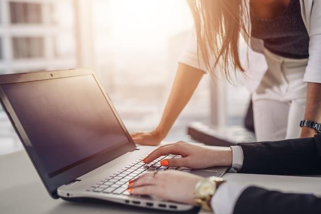 Team creativo che utilizza internet digitando sulla tastiera del laptop nell'edificio per uffici.