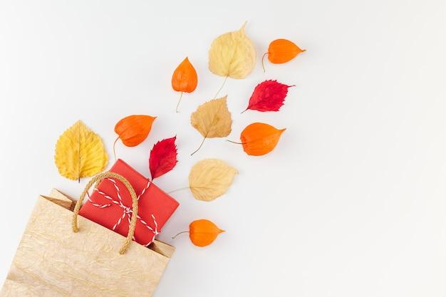 Creativo vista dall'alto piatto laico composizione autunnale borsa per la spesa fiori d'arancio secchi foglie sfondo copia spazio modello vendita mockup raccolta autunnale ringraziamento halloween promozione volantini