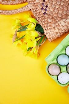 Creative top view flat laici primavera composizione shopping sacchetto di paglia narciso bouquet di fiori, uovo di pasqua su sfondo giallo