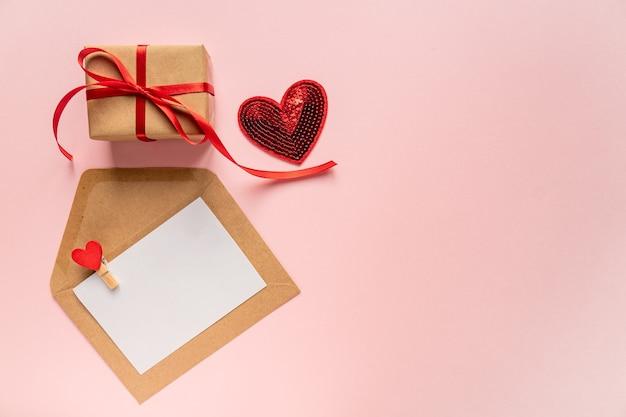 Composizione romantica creativa di san valentino con busta di carta, cuore rosso e confezione regalo
