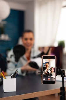 Vlogger creativo e influencer che filma una recensione di cuffie vr in un podcast di studio professionale. i social media nell'era del web digitale su internet registrano nuovi video per il pubblico online
