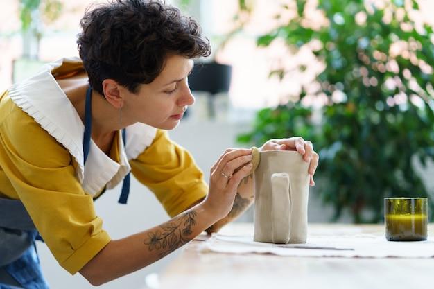 Donna creativa che modella la brocca di argilla in studio artista femminile con tatuaggi lavora su ceramica in officina