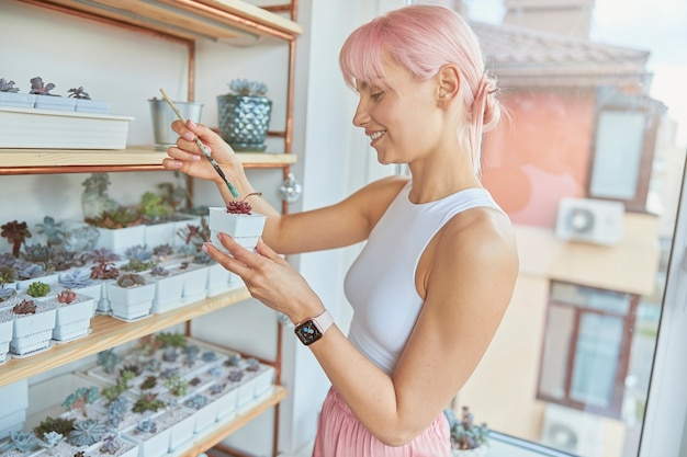 La donna creativa dipinge piante d'appartamento esotiche in colore verde sul balcone chiaro