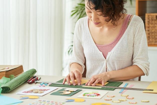 Donna creativa che usa un righello di metallo quando taglia la carta colorata su un tappetino da taglio verde per realizzare biglietti di auguri
