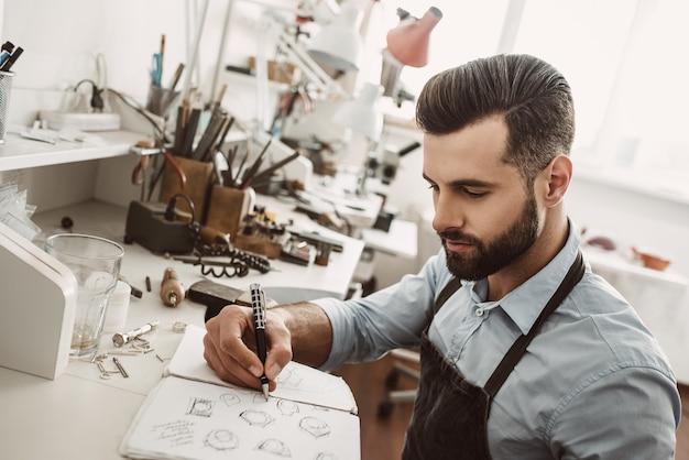 Lavoro creativo. ritratto di giovane gioielliere barbuto che disegna uno schizzo di un nuovo anello nel suo laboratorio