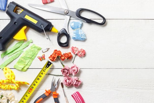 Concetto creativo del posto di lavoro: vista superiore del tavolo con elementi per scrapbookin e strumenti per la decorazione