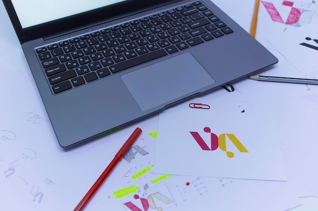 Luogo di lavoro creativo di un grafico. sviluppo di un logo per l'azienda. disegni e schizzi su carta nell'ufficio di uno studio d'arte.