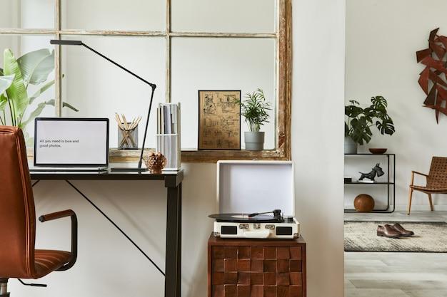 Composizione creativa dell'area di lavoro di interni maschili moderni per l'home office con scrivania industriale nera, poltrona in pelle marrone, laptop, giradischi vintage e accessori personali eleganti. modello.