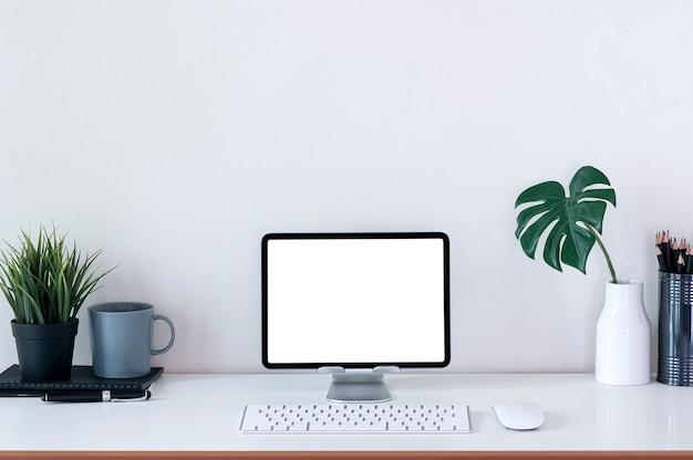 Modello creativo dell'area di lavoro con tablet schermo vuoto su supporto e tastiera su tavolo bianco.
