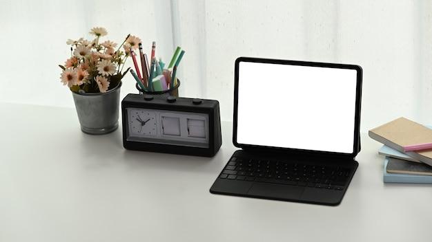 Area di lavoro creativa con tablet computer schermo vuoto e forniture sul tavolo bianco.