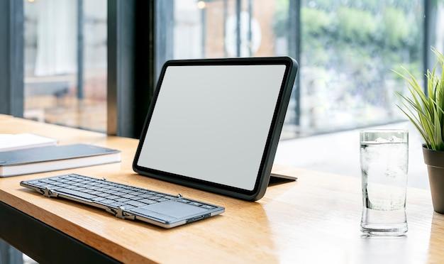 Area di lavoro creativa con tablet e tastiera a schermo vuoto su bancone in legno nel soggiorno.