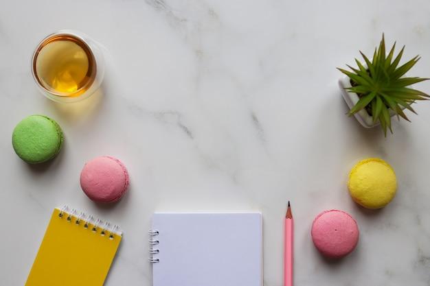 Area di lavoro creativa con quaderni, matita, pianta, tazza di tè e amaretti con copia spazio