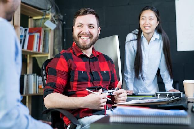 Giovani creativi che godono del lavoro in ufficio