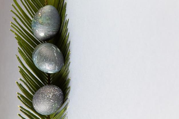 Uova di pasqua di pollo dipinte in modo creativo con colorante di ibisco naturale, assomigliano a pietre di mare, foglia di palma da dattero su sfondo grigio, spazio di copia