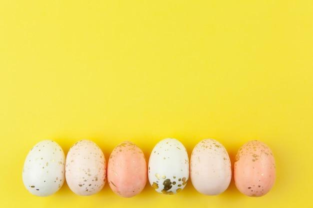 Le uova dipinte in modo creativo in colori pastello e decorate con foglia d'oro sono disposte in fila su sfondo giallo