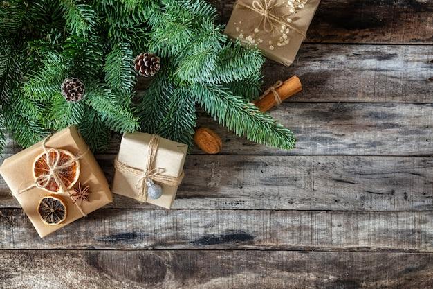 Regali di natale creativamente avvolti e decorati in scatole dal brunch fresco dell'albero di natale su superficie di legno scura, disposizione piana, spazio della copia Foto Premium