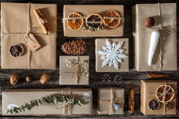 Regali di natale confezionati e decorati in modo creativo in scatole su superficie di legno scuro, distesi piatti,