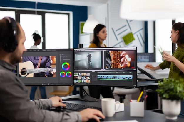 Contenuti del creatore che indossano le cuffie che modificano il montaggio del film nel software di post produzione sul computer con configurazione a doppio monitor