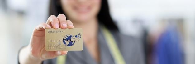 Carta di plastica della banca di credito nel concetto di pagamenti con carta di credito della mano della donna Foto Premium